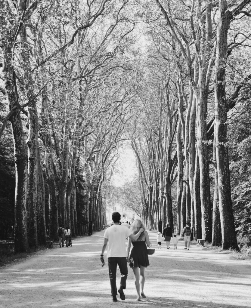 A black and white photograph of people walking through a road surrounded by tall trees.