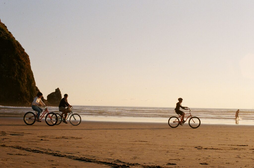 A photograph of 3 bikers on a sandy beach during sunrise or sunset. There is a person in the background playing in the water.